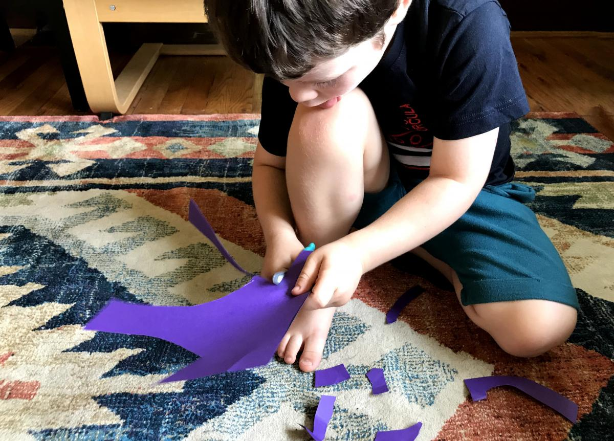 A photograph of a young child cutting purple construction paper.