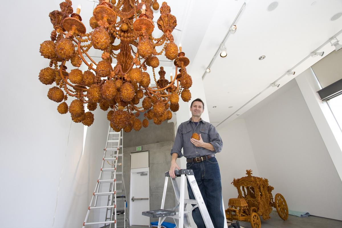 A photograph of an artist installing and artwork in a gallery.