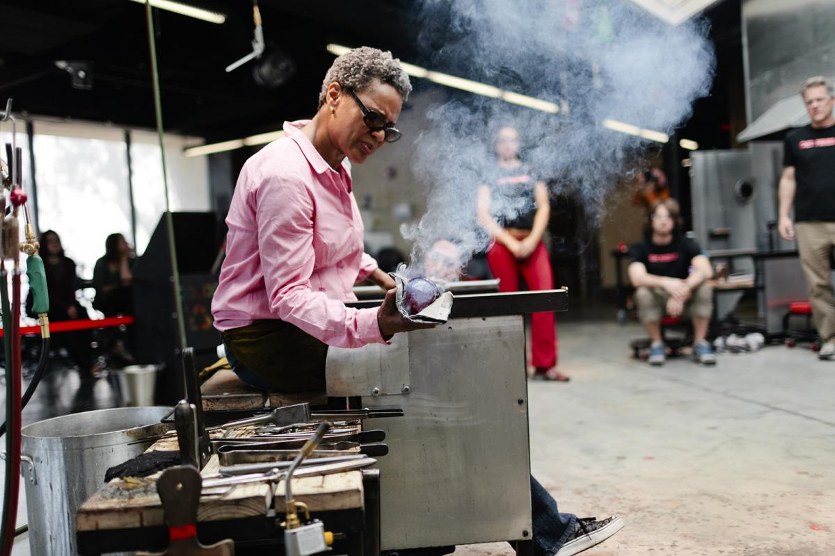 A photograph of a woman in a studio blowing glass.