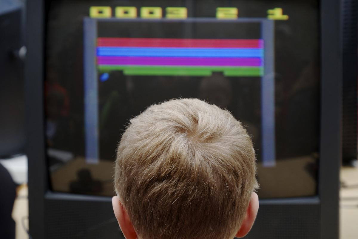 The back of a child's head with a video game in front of them.