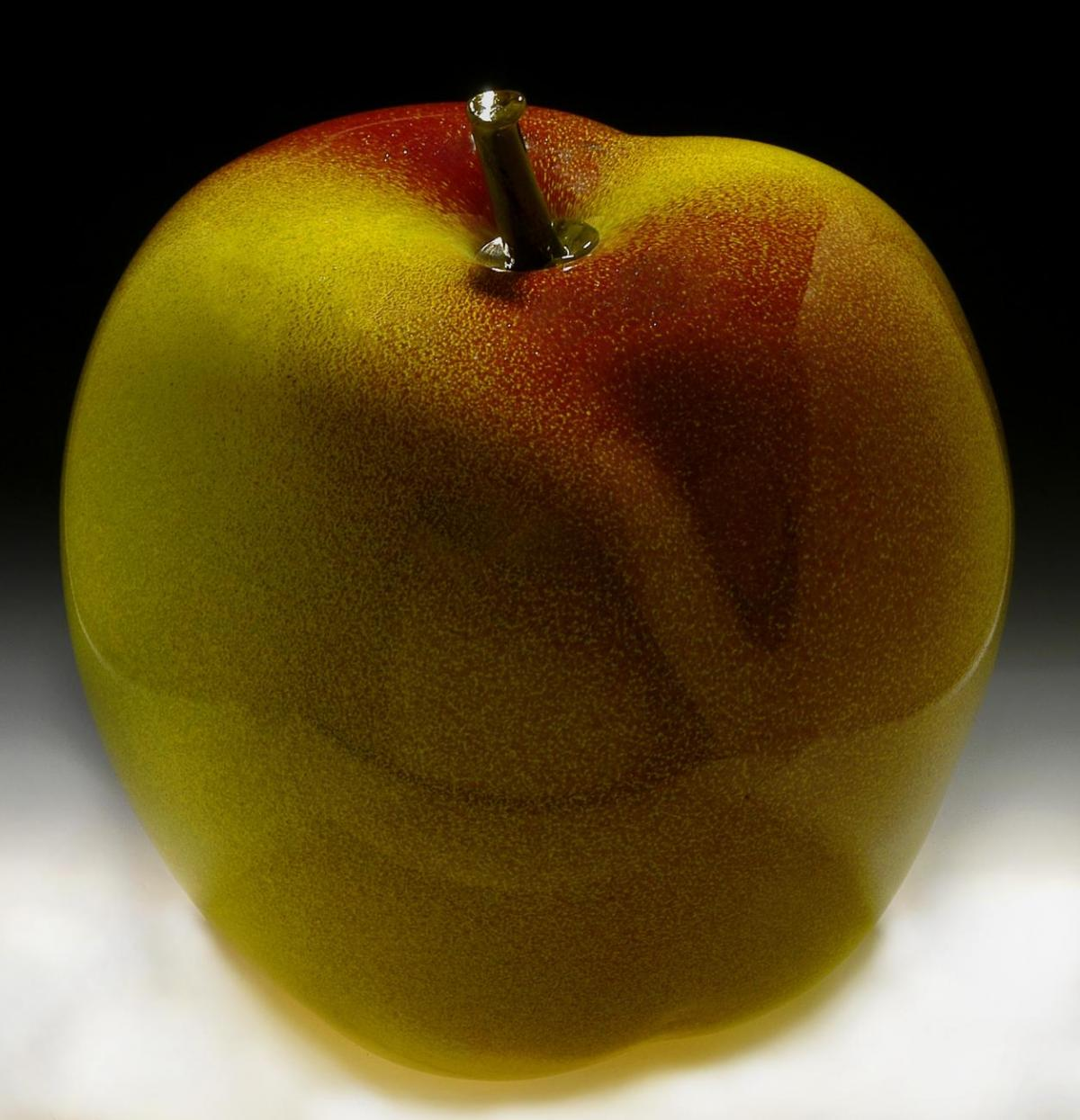 A photograph of a large apple made of glass.