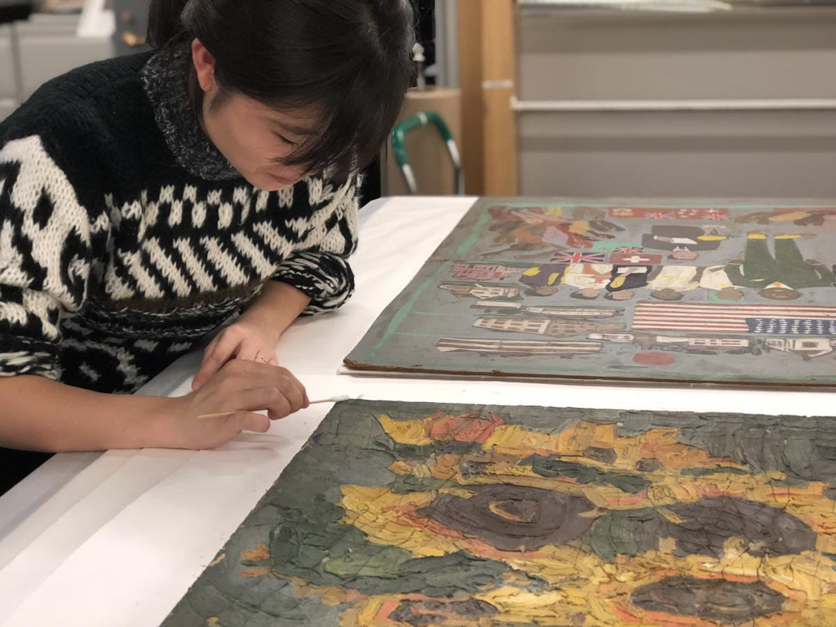 A conservator working on a painting