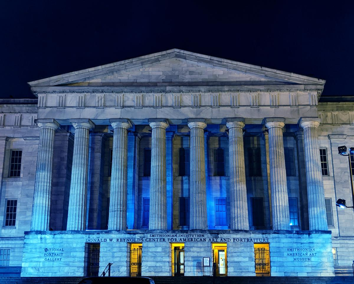 A photograph of the facade of the Smithsonian American Art Museum at night with blue lights honoring healthcare workers.