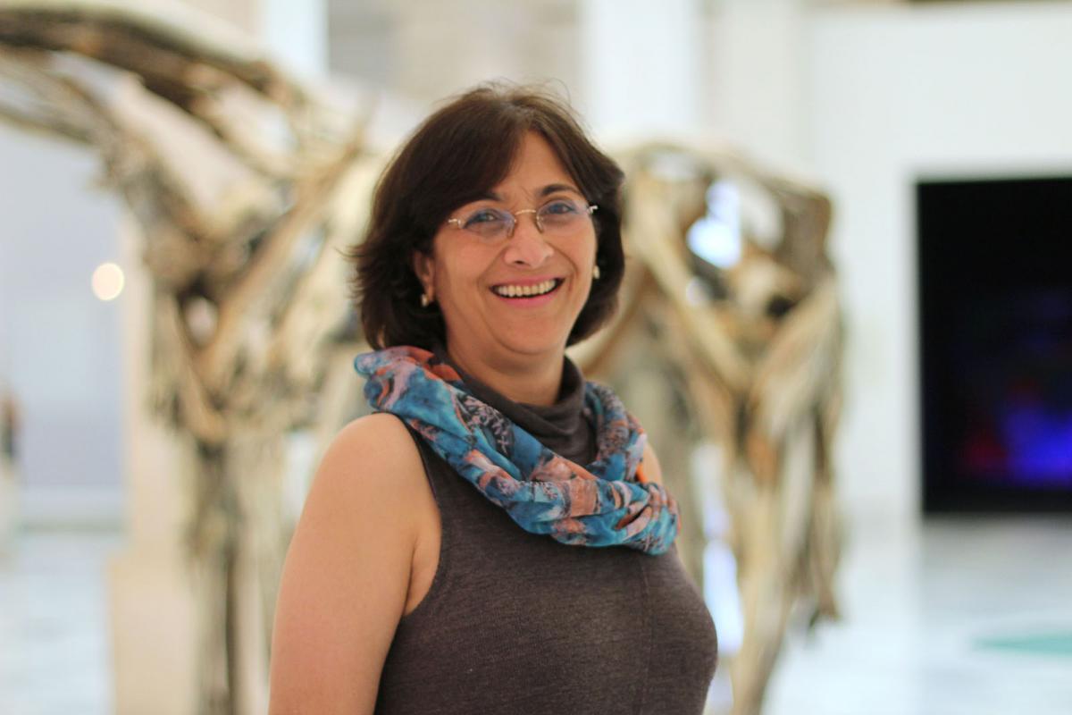 A photograph of a woman inside an art gallery.
