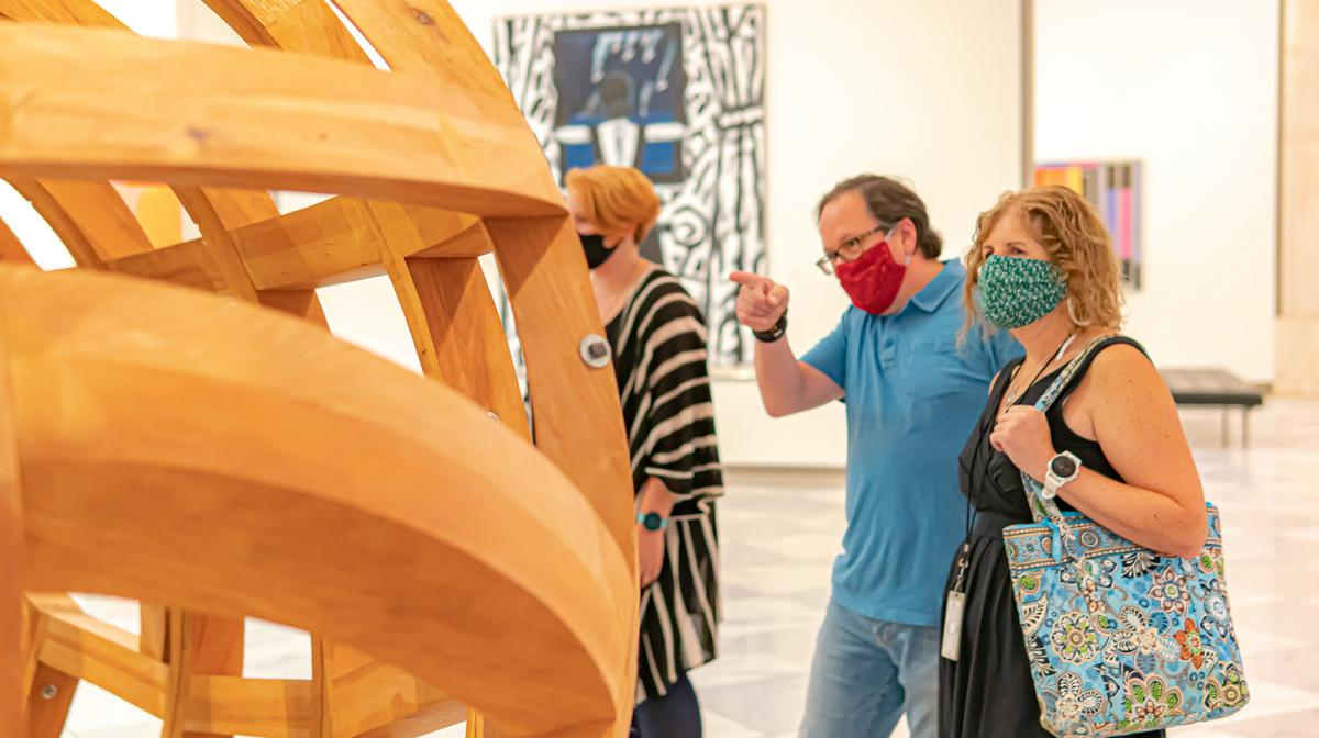 A photograph of people looking at art in the galleries with masks on.