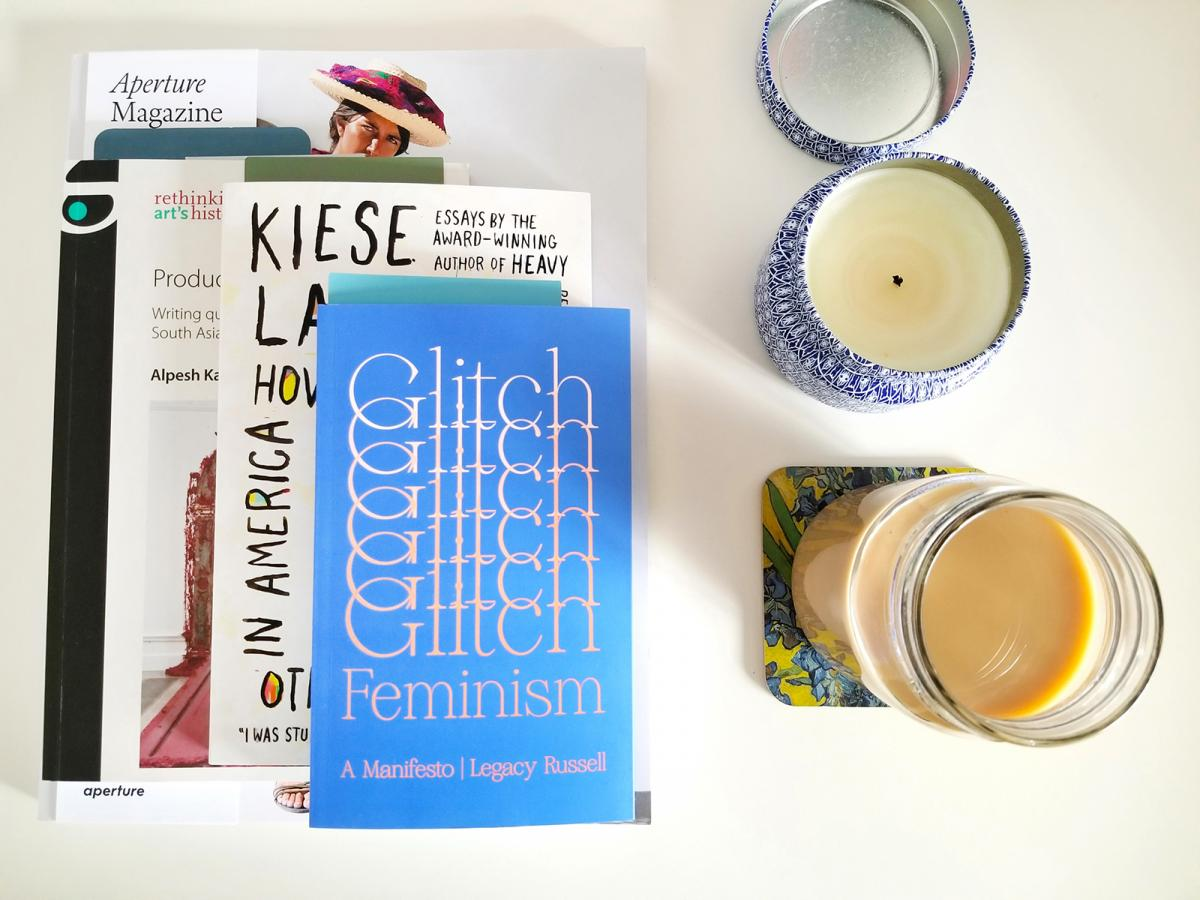 A photograph of books on a table with candles