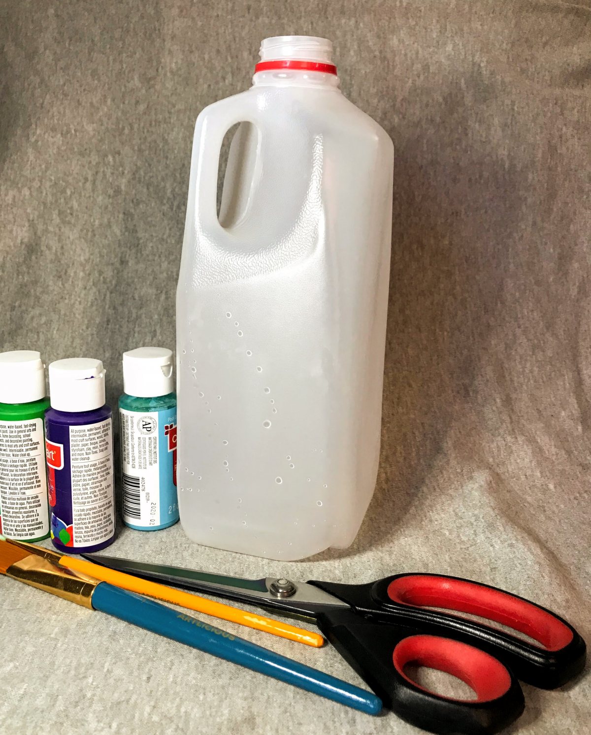 A grouping of supplies: milk jug, paint, and scissors