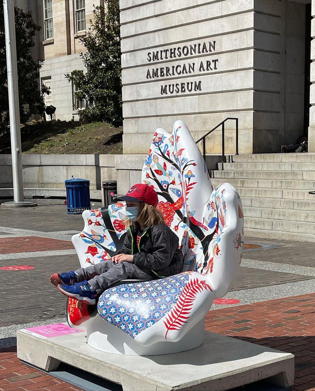 Child sitting in Rashin Kheiriyeh Cherry Garden chair