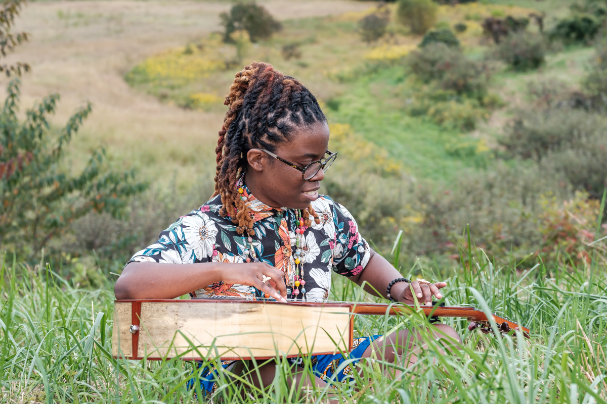 photo of Yasmin Williams playing guitar while sitting in the grass