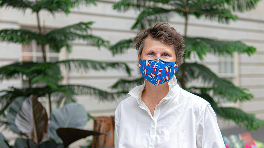 A woman in a blue mask standing in front of plants.