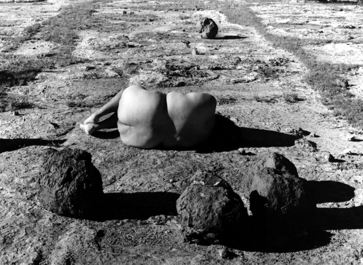 A black and white photograph showing the back of a nude woman lying down on the ground, surrounded by rocks.