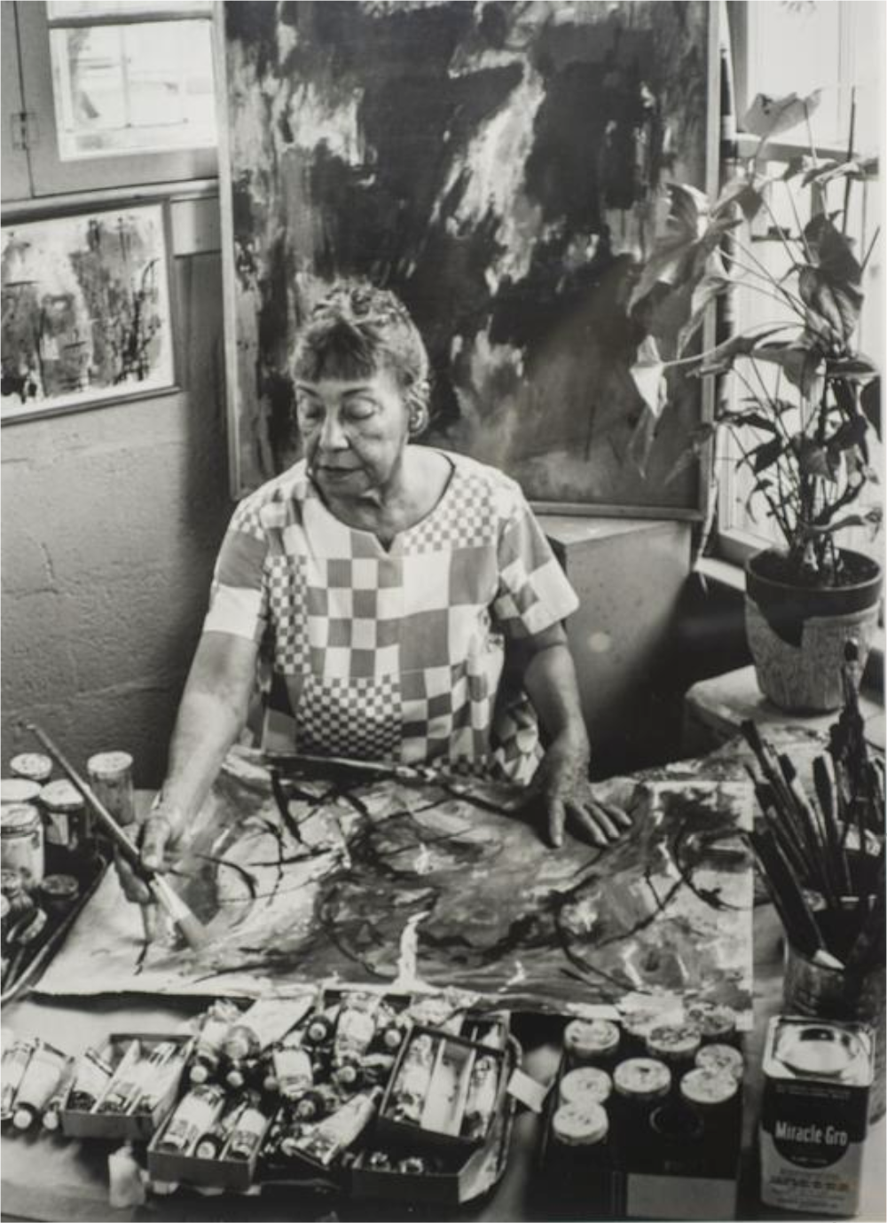 A black and white photograph of artist Alma Thomas painting in her studio.