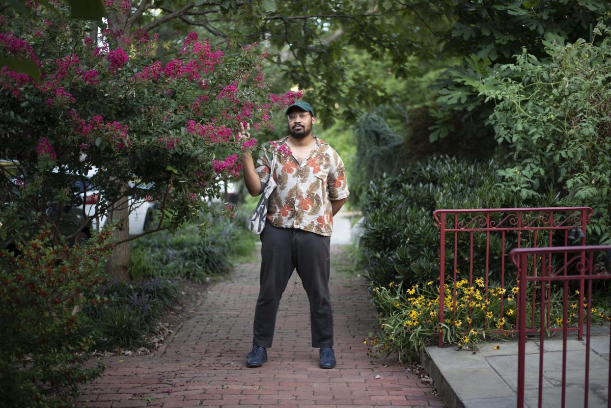 A photo of musician Bartees Strange standing on a sidewalk between trees