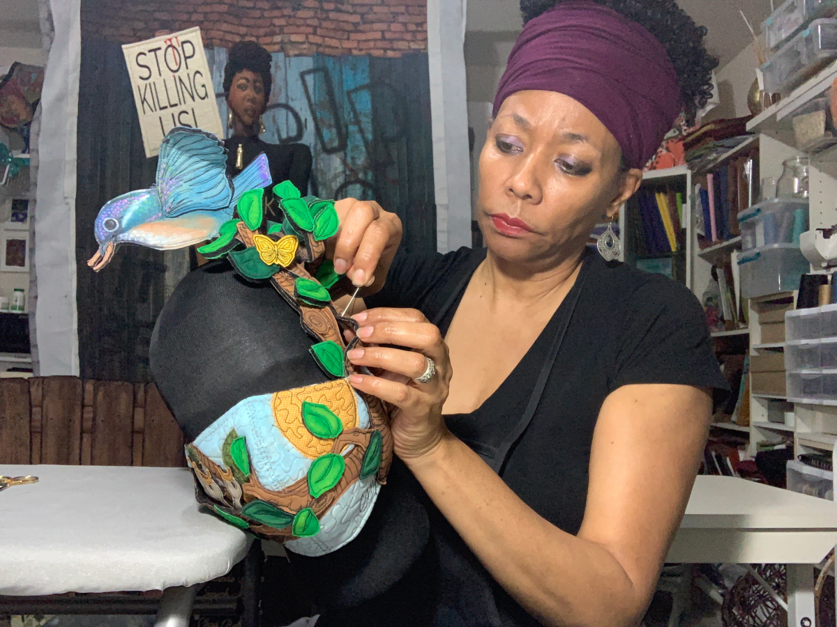 A close up of the artist in her studio making a mask with a motif of leaves, butterflies and birds