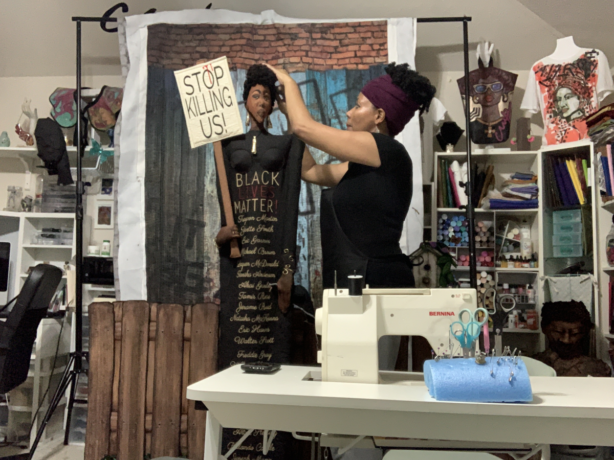 The artist standing near her sewing machine working on a Black Lives Matter artwork