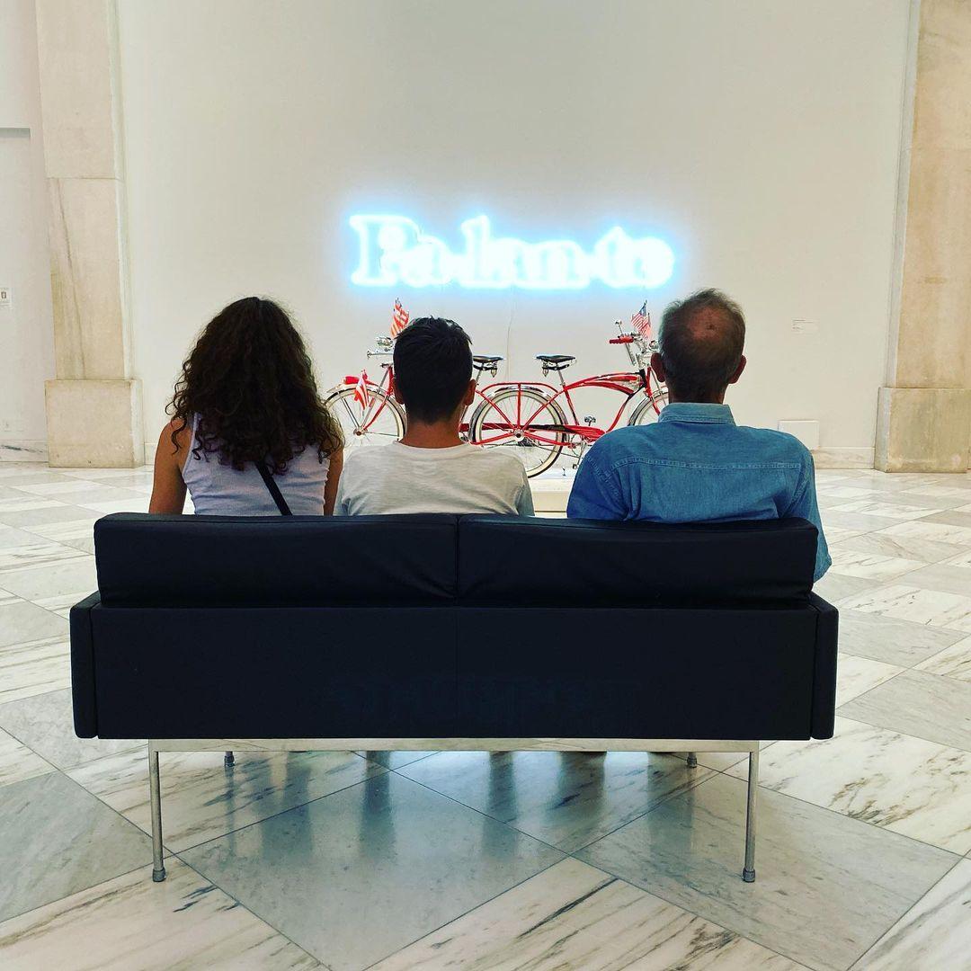 "Three people sitting on a sofa looking at neon sign artwork ""Pa-lan-te"""