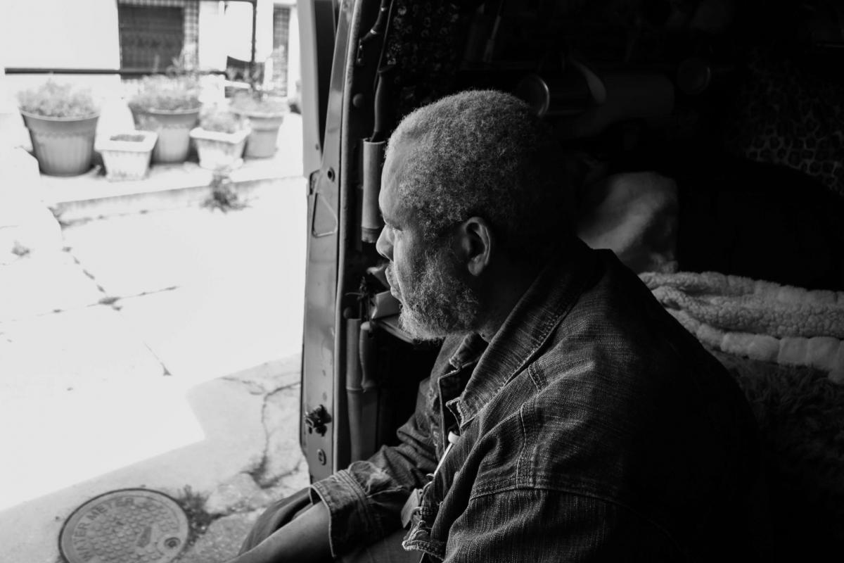 Black and white photo of an African American man sitting in the shade of a car interior, looking out onto a brightly lit sidewalk.