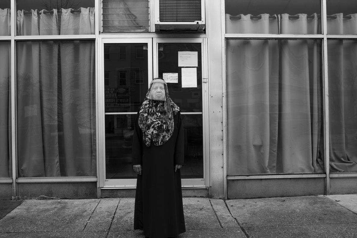 Black and white photo of an African American woman wearing a swirl-printed hijab and protective face shield stands outside a buidling with large plate-glass windows.