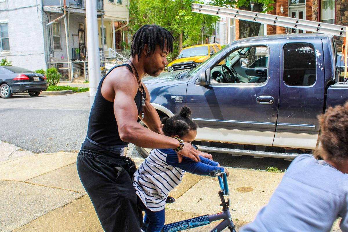 A muscular African American man helps a small child ride a large bike. Another child can be seen at the extreme foreground. Work trucks are parked along the street.