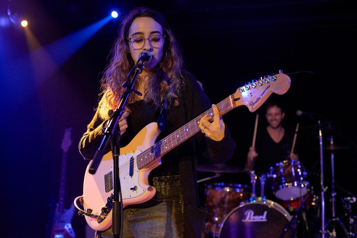 Rachel Kline, of the band Flowerbomb, plays a guitar on a stage