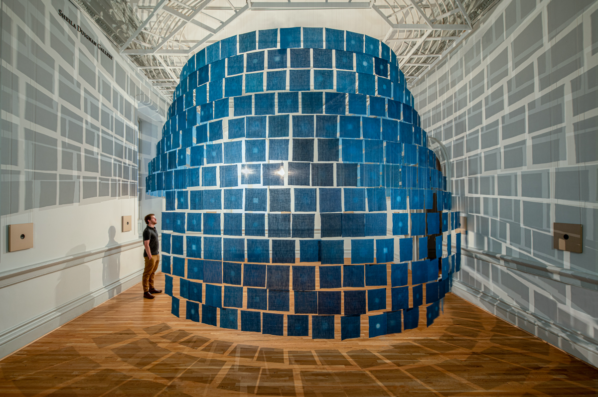An installation view of small indigo cloths hanging from the ceiling
