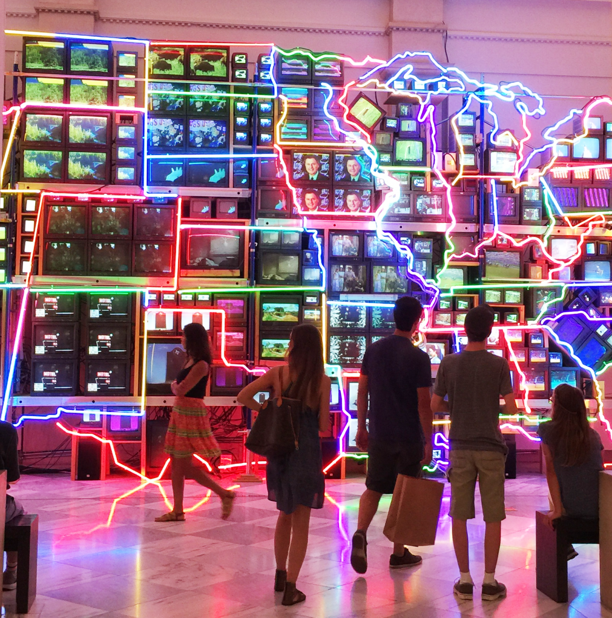 """Visitors viewing """"Electronic Superhighway"""" installation, made up of video monitors and neon lights."""