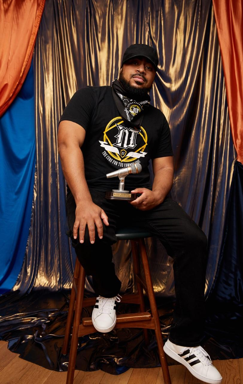 Emcee, Night Train 357, poses with his WAMMIE award in front of a gold curtain.