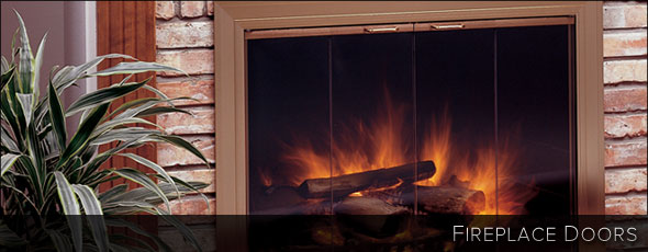 Glass fireplace door with shiny gold trim in a red brick wall