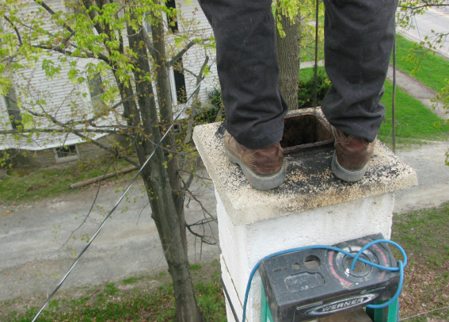 Chimney sweep's feet standing on a white stone chimney