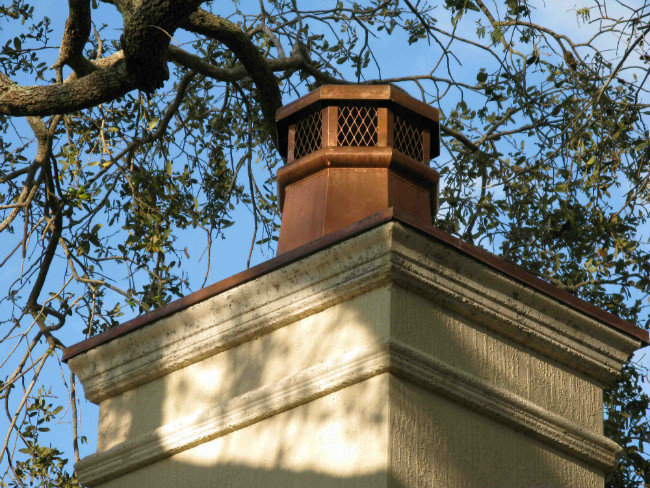 Copper chimney cap on a masonry chimney with trees hanging overhead