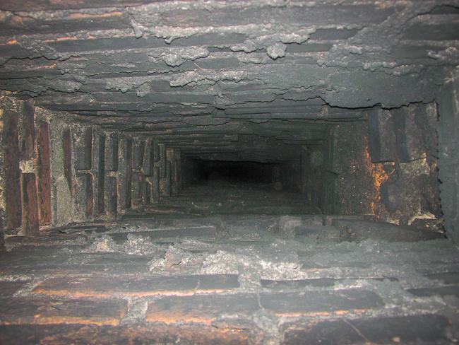 Black creosote residue inside a red brick chimney