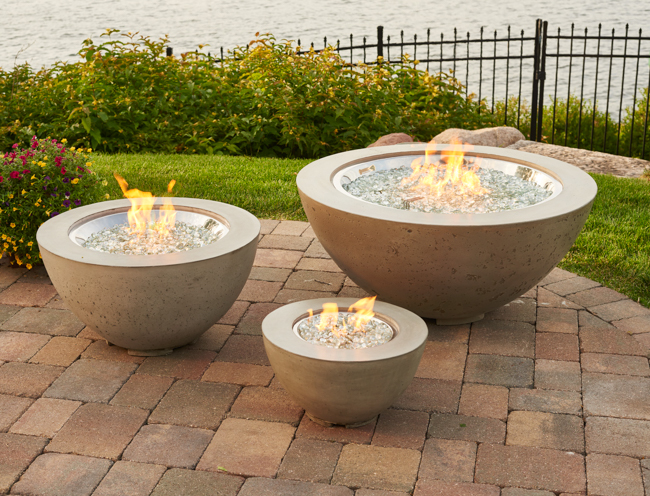 Three fire bowls on a concrete patio