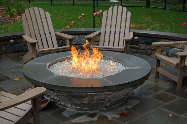 Close-up of a gray stone fire pit with crystal fire glass