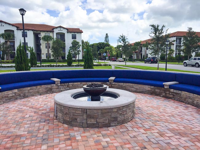 Round masonry stone fire and water fountain in a brick plaza