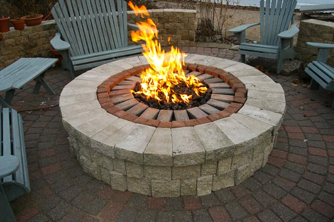 Close-up of a stone fire pit with large flames