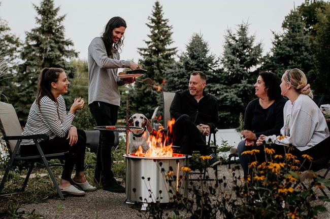 Family gathered around a stainless steel wood burning fire pit