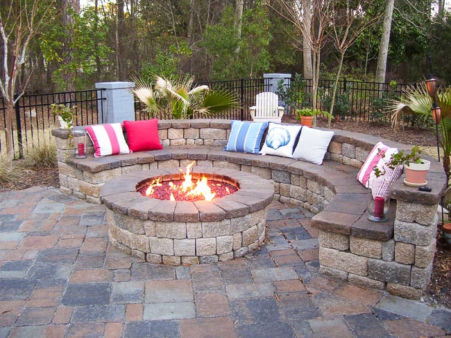 Round maonsry stone fire pit with red fire glass and bright flames surrounded by a half-moon bench seat