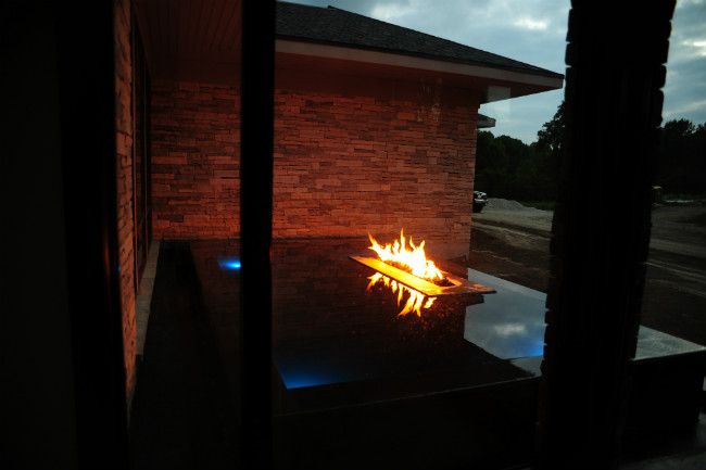 Back view of a dark stone linear infinity reflecting pool with an embedded burning linear fire pit