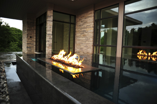 Dark stone linear infinity reflecting pool with an embedded burning linear fire pit