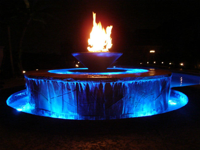 Water fountain with vibrant blue LED lights and a fire bowl on top at night