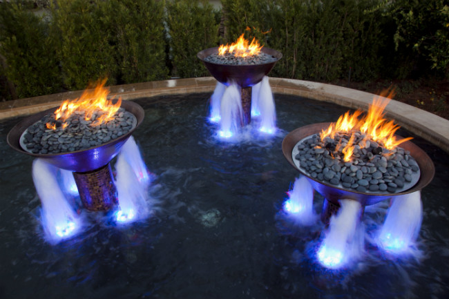 Three fire bowls in a fountain with four illuminated jets of water shooting out of the bottom of each bowl