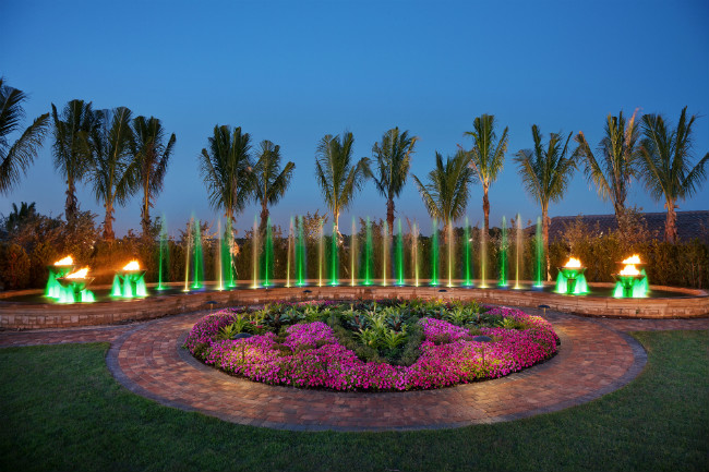 Nighttime view of a garden in front of a large curved fountain with fire and water bowls and illuminated water jets