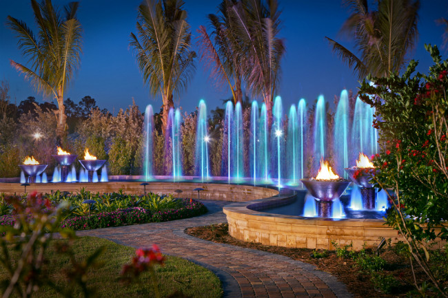 Fire and water bowls surrounding blue illuminated water jets shooting out of a fountain at night
