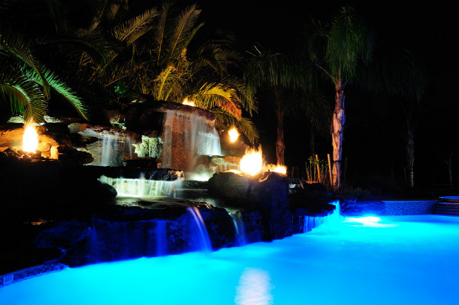 Night view of blazing fire rocks and waterfalls flowing into an aquamarine pool