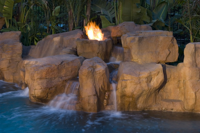 A rock with fire coming out of it and waterfalls flowing into a swimming pool
