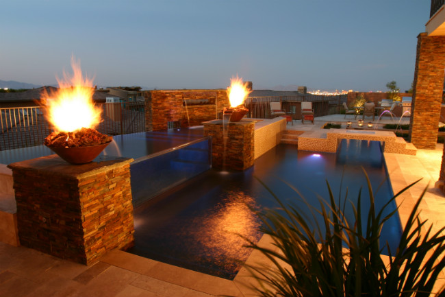 Two fire and water bowls on either side of a contemporary swimming pool at night