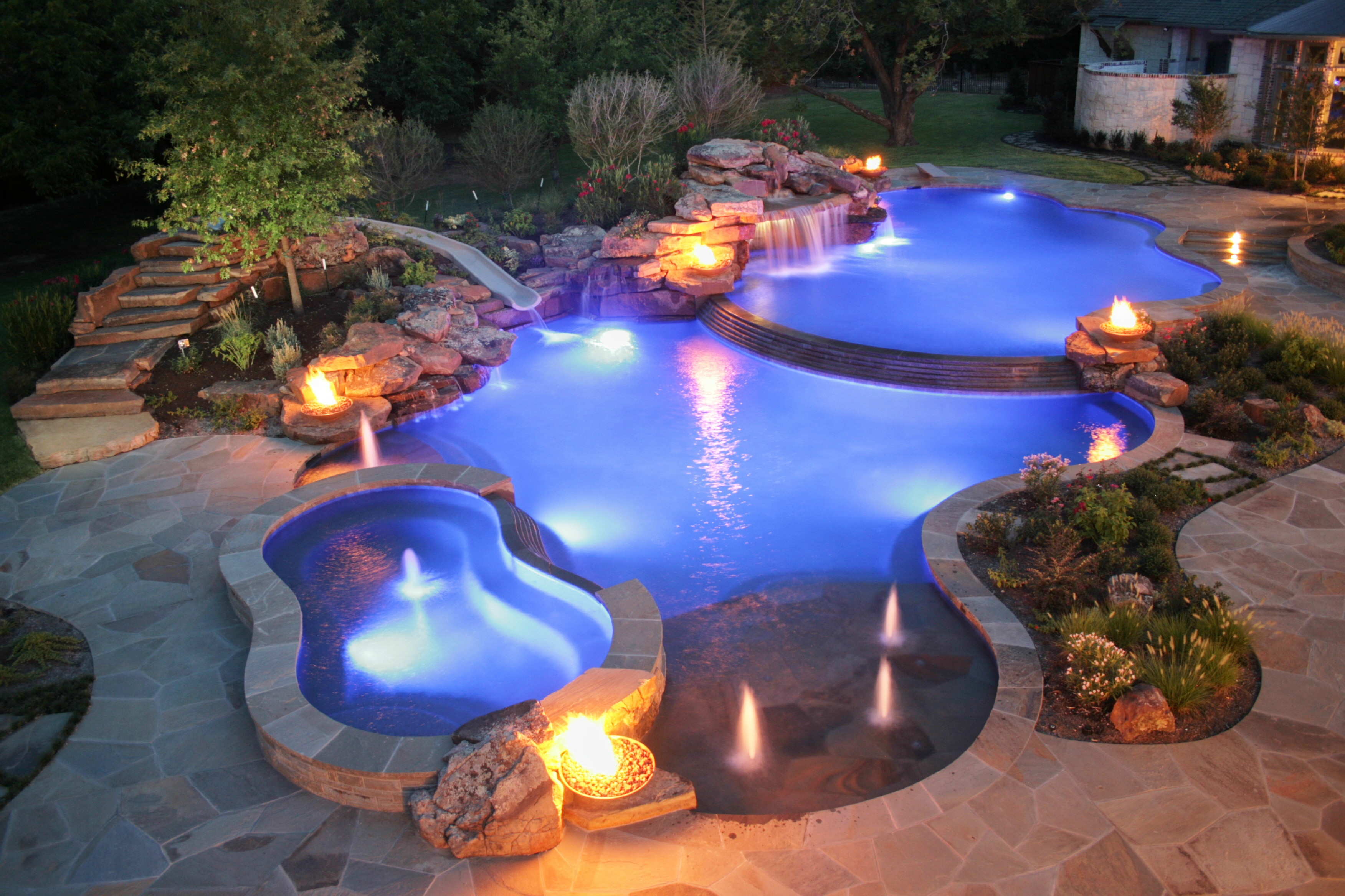 A stone patio with greenery and fire bowls surrounding a vibrant blue swimming pool