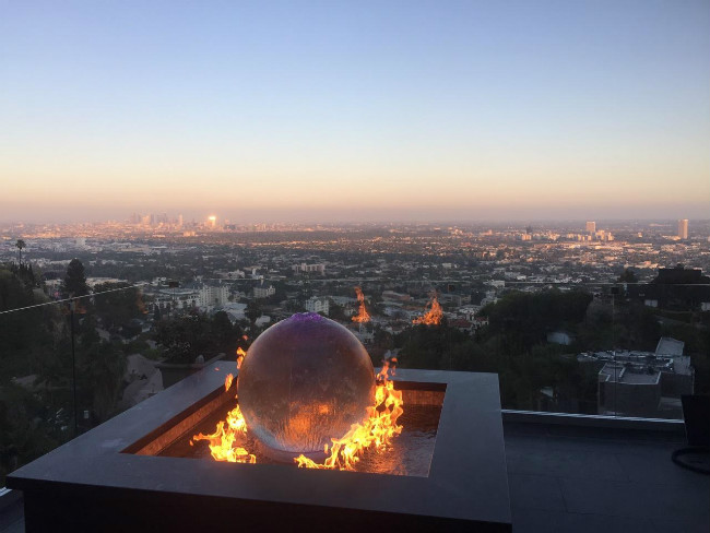 Square fire fountain with a globe in the center on a rooftop overlooking Los Angeles