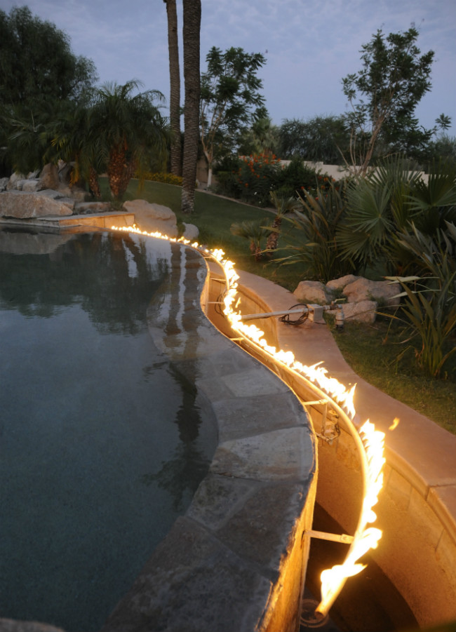 Flames lining the curved edge of an infinity swimming pool