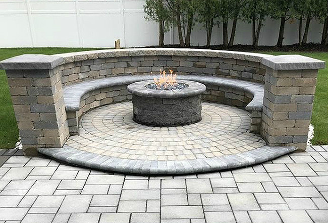 Masonry fire pit in the middle of a stone patio